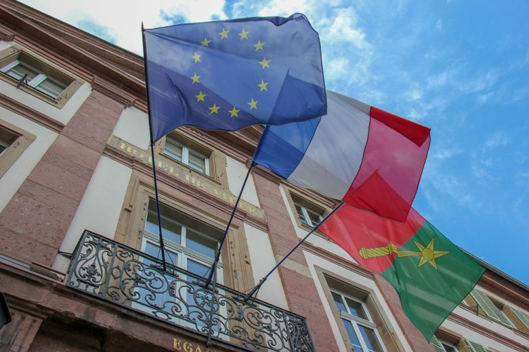 Colmar, France and EU flags flying from building in Colmar, France