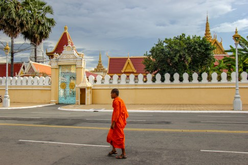Monk walks past Royal Palace in Phnom Penh, Cambodia