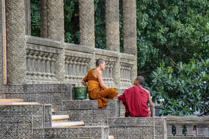 Two monks sitting on stairs at Moha Montrei Pagoda in Phnom Penh, Cambodia
