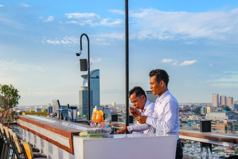 Bartenders making cocktails at rooftop SkyBar at SIM Boutique Hotel in Phnom Penh, Cambodia