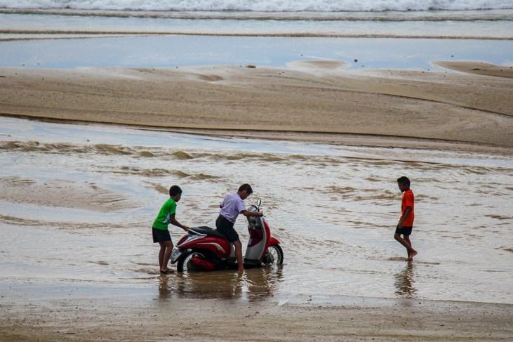 Kids driving scooter on beach at Kamala Beach on Phuket, Thailand