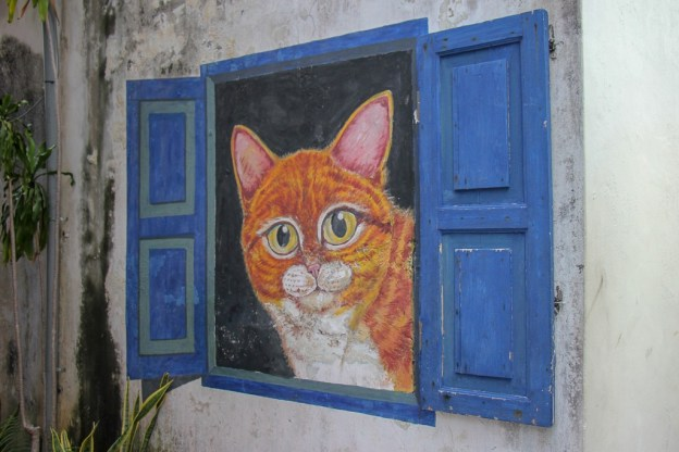 Cat peeks outside wall art mural in Geroge Town, Penang, Malaysia