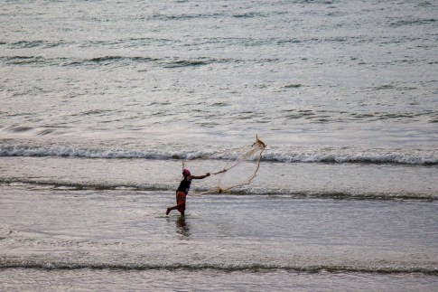 Fisherman casts net at Kamala Beach on Phuket, Thailand