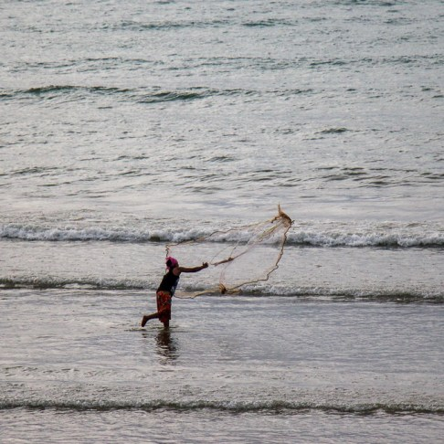 Fisherman casts net at Kamala Beach on Phuket, Thailand