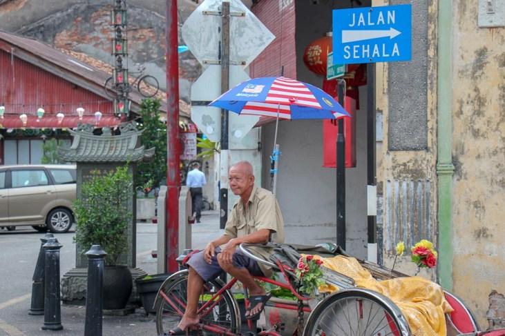 Trishaw driver sits on street corner in Geroge Town, Penang, Malaysia