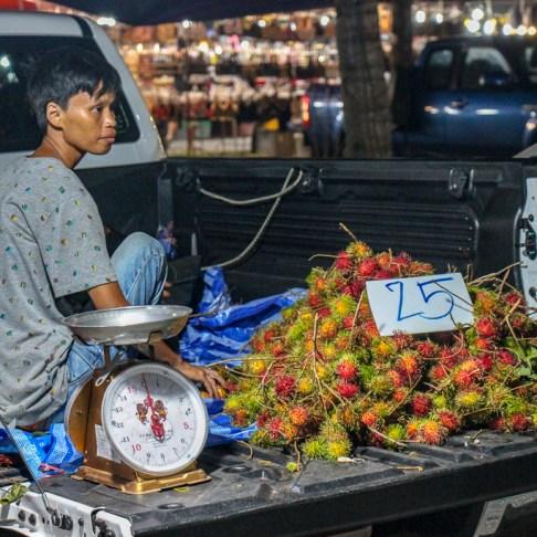 Man sells Rambutan Fruit from pickup truck at Friday Night Market in Kamala Beach on Phuket Island, Thailand