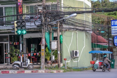 Wires and scooters street scene in Kamala Beach on Phuket, Thailand