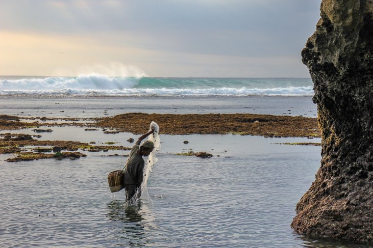 Local fisherman with net at Suluban Beach in Uluwatu, Bali, Indonesia