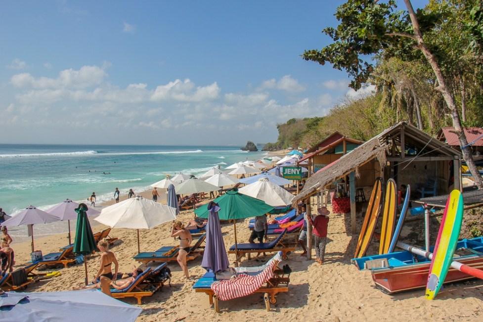 Beach umbrellas and loungers at Padang-Padang Beach in Uluwatu, Bali, Indonesia