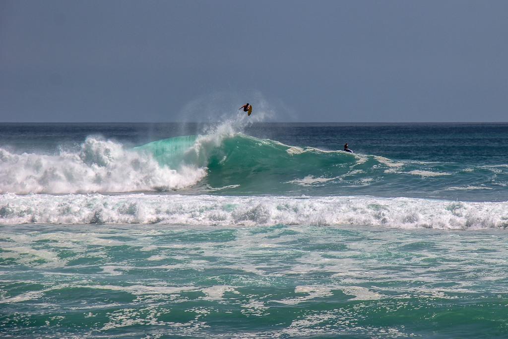Surfer catches air while riding wave in Uluwatu, Bali, Indonesia