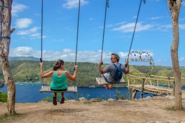 Swinging on swings over cliff at Ceningan Cliffs Restaurant on Nusa Ceningan, Bali, Indonesia