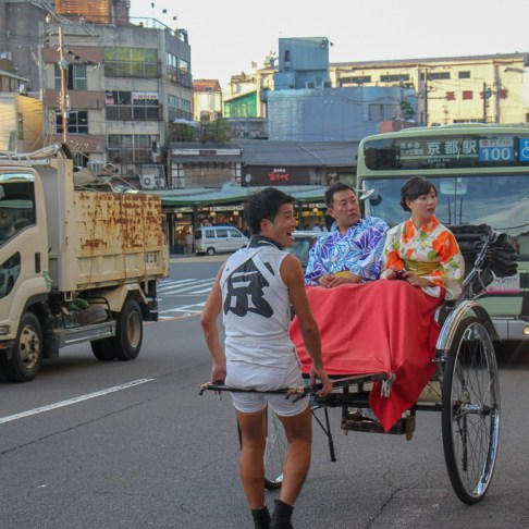 Couple rides in rickshaw in traffic in Kyoto, Japan