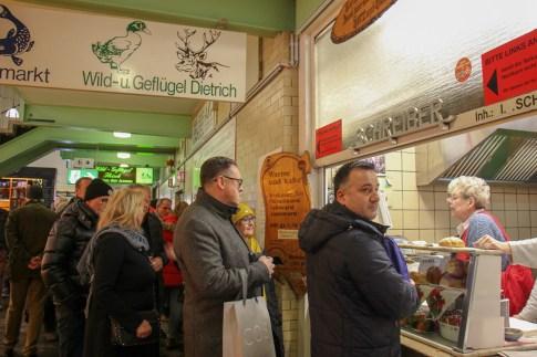 People wait in line for Frau Schreiber sausages at Klienmarkthalle in Frankfurt, Germany