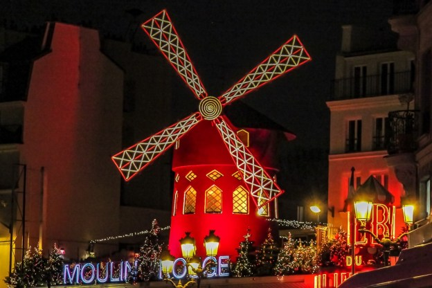 Red Windmill of Moulin Rouge at night in Paris, France