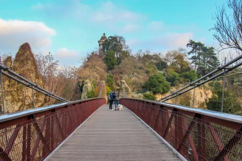 Walking across bridge in Parc des Buttes-Chaumont in Paris, France