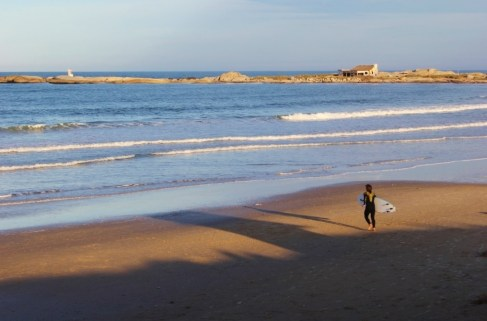 Surfer in wetsuit runs across beach in Punta del Diablo, Uruguay