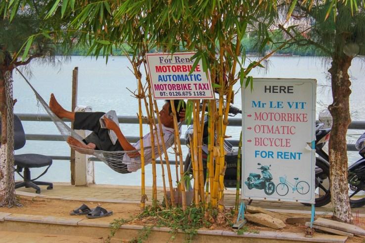 Man in hammock rents bikes in Hoi An, Vietnam