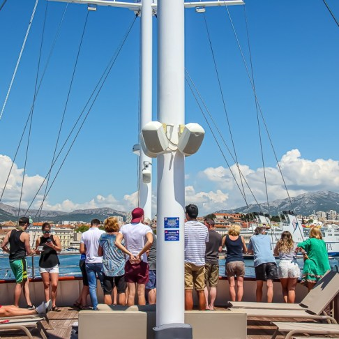 Passengers stand on top deck on arrival to Split during our Adriatic Sea Cruise
