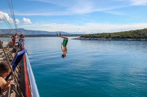 Man flipping from top deck of Almissa ship on Sail Croatia Explorer Croatia Island Hopping Cruise
