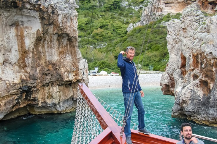 Captain Jure stands on bow of ship at Stiniva Beach on Vis Island, Croatia