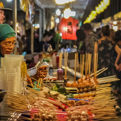 Sticks of food for sale by Food Cart Vendor at Train Night Market in Bangkok, Thailand