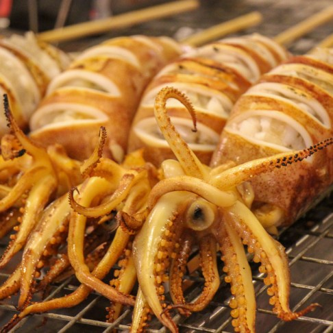 Fresh grilled squid on a stick for sale at the Train Night Market in Bangkok, Thailand