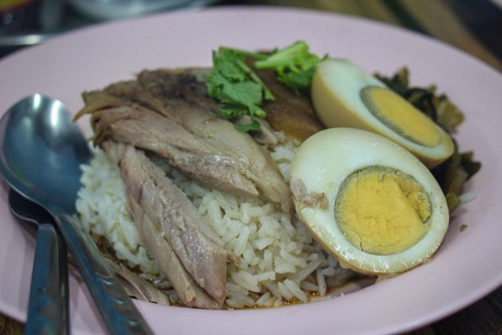 Plate of stewed pork leg with rice and boiled egg at Pig Trotter Restaurant in On Nut Bangkok, Thailand