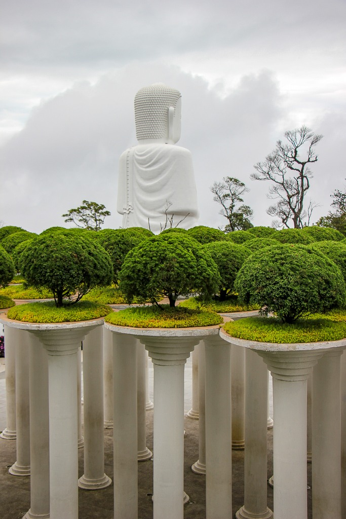 Buddha Statue rises above Flower Garden at Ba Na Hills in Da Nang, Vietnam