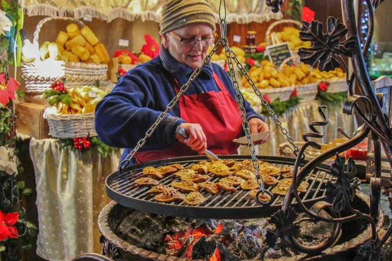 Woman grilling oscypek cheese at Krakow Christmas Market
