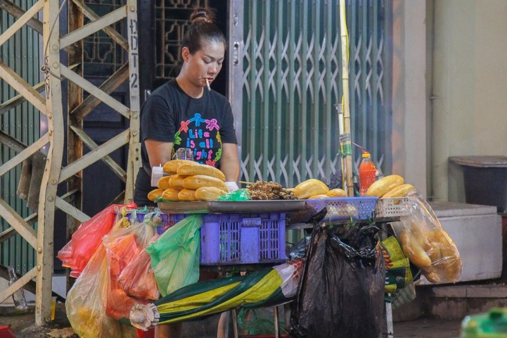 Woman makes sandwiches at Banh Mi Cart in Hanoi, Vietnam