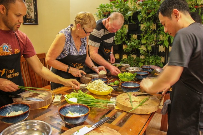 Class participants working together to make meal at Rose Kitchen Cooking Class in Hanoi, Vietnam