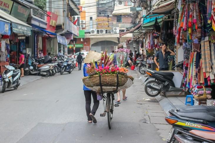 Woman pushes bike with basket of flowers through Old Quarter Hanoi, Vietnam