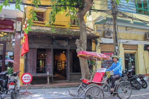 Man pedals cyclo past Ancient House in Hanoi, Vietnam