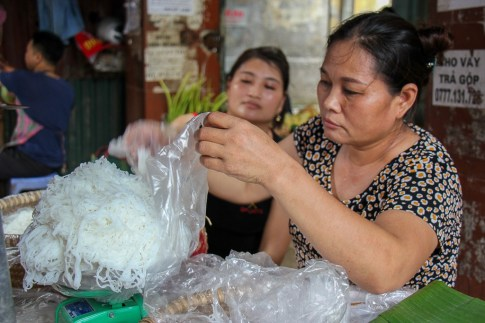 Buying rice noodles from vendor at local market in Hanoi, Vietnam