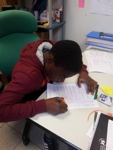 Jeune rédigeant une lettre de motivation à l'accueil jeunes de Veigné