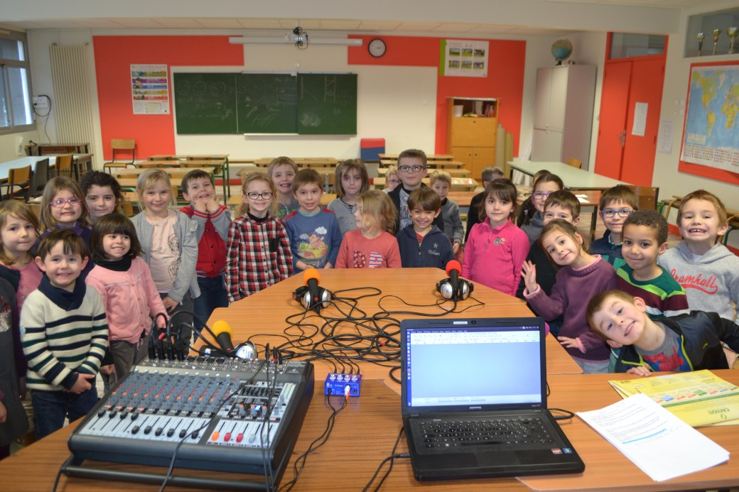 Nous voyons une vingtaine d'enfants de l'école primaire d'Artannes être en demi cercle autour des micros, afin de chanter une chanson venant conclure l'enregistrement de l'émission réalisée