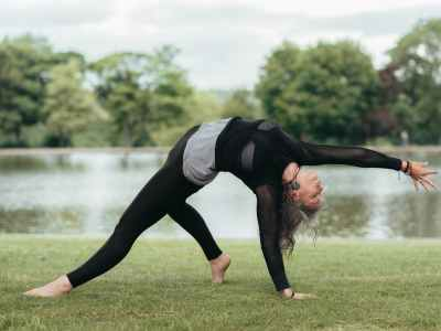 flexible woman performing wild thing pose on grass coast