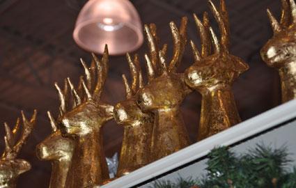 A line of golden deer peeking over the top shelf.