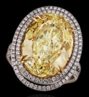 The large yellow diamond is accented by round brilliant colorless diamonds and set in platinum and 18k yellow gold.
