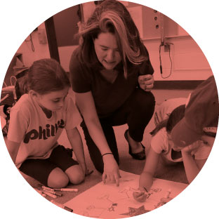 An image of a woman sitting with three young children and helping them as they color and create a picture with their crayons.
