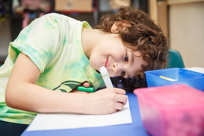 Young student coloring at his desk