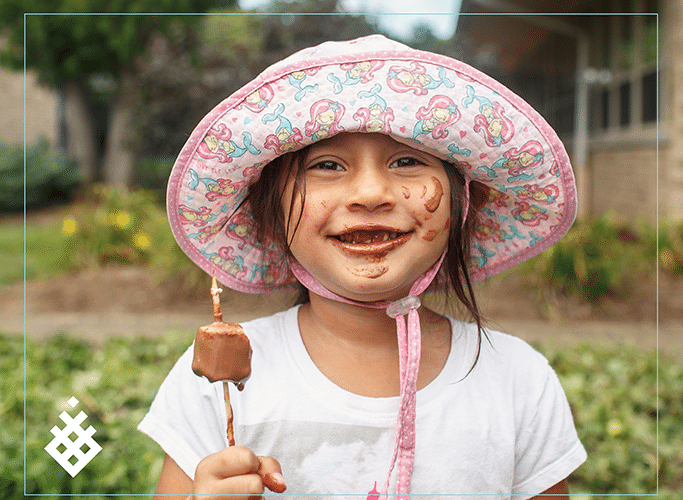 Young child with chocolate on her face at camp