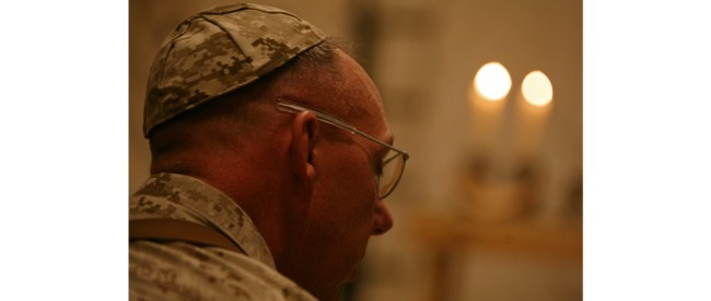 Jewish New Year - a Time for Reflection of Inner Self: Col. Kevin Vest, the commanding officer of Marine Aircraft Group 40, Marine Expeditionary Brigade-Afghanistan, follows along in prayer at a Rosh Hashanah service, Sept. 18, 2009, at Camp Leatherneck in Helmand province, Afghanistan. The process of reflection and repentance takes place over a 40-day period that begins about four weeks before Rosh Hashanah, at the start of the month known as Elul on the lunar Jewish calendar. (Photo by Cpl. Aaron Rooks)