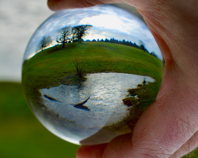 Frozen pond through a lensball