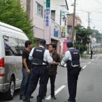 福島第一原発から約5㌔離れた大熊町の商店街にて。県外からも警察官がパトロールに訪れている。巡回中の警察官にインタビューをする大学院生ら/2016年5月24日