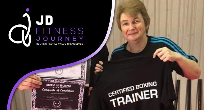 Image of Jude Davis holding up her certified boxing tshirt and certificates