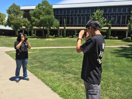 Two bored photographers take pictures of each other. (Photo credit: Aryanna Zavala)