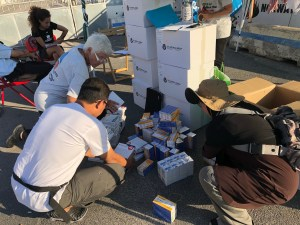 International and local volunteers inventory emergency medical supplies in the port of Naples.