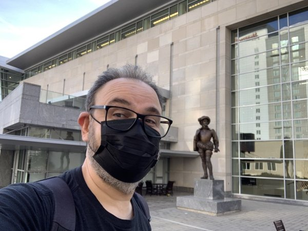 """Jean-Georges """"jgp"""" Perrin standing next to the statue of Sir Walter Raleigh in front of the Raleigh Convention Center."""