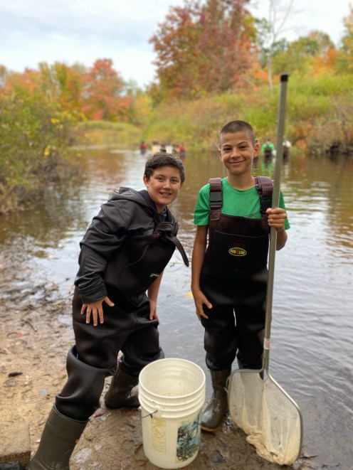 Seventh grade students Joseph Duchemin, left, and Eric Barnett collect samples at Lamprey River. (Courtesy Photo Raymond School District)